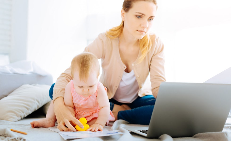 working mother playing with baby while looking at laptop, for back from maternity leave common challenges feature
