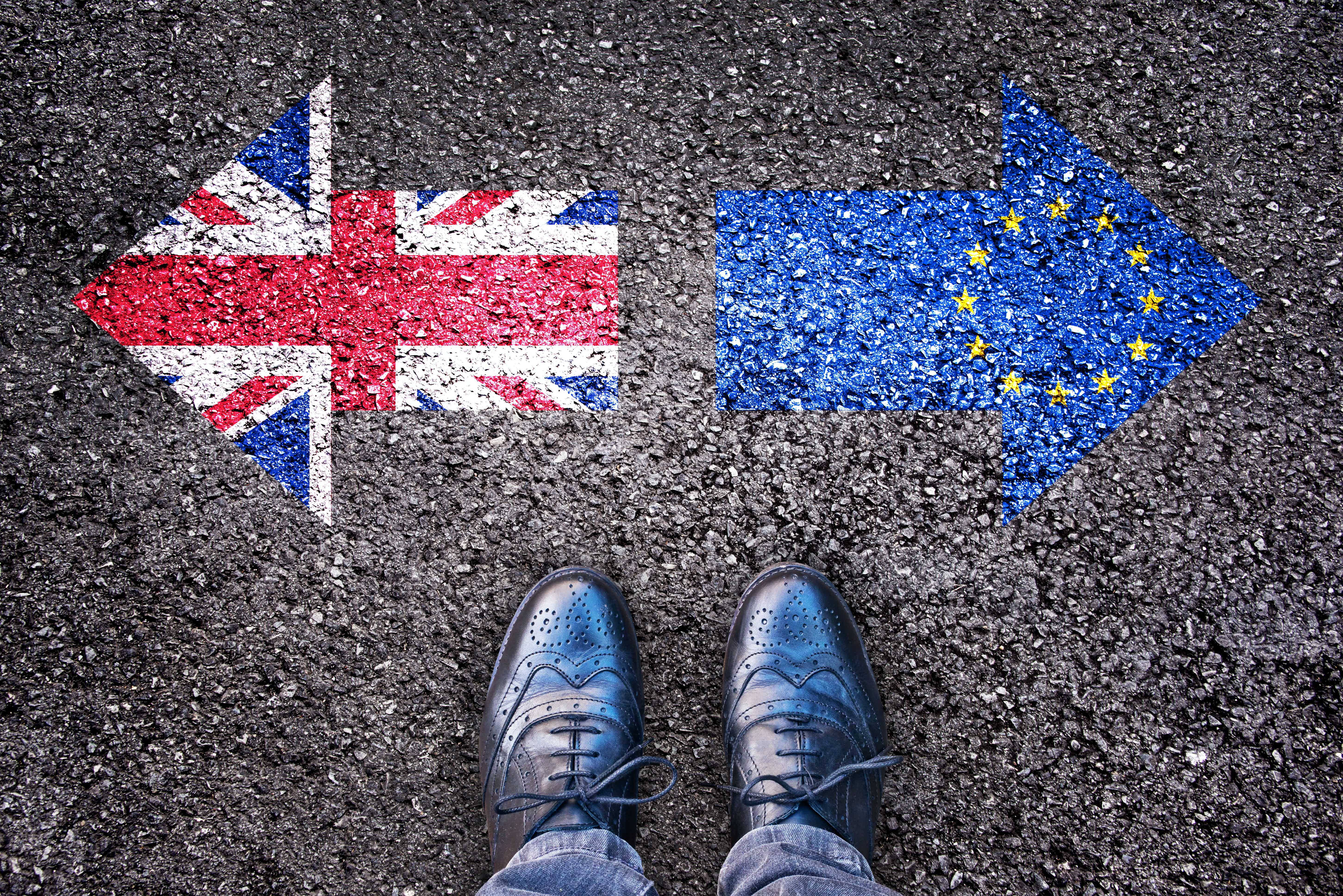 Brexit, flags of the United Kingdom and the European Union on asphalt road with legs