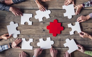 Teamwork concept shown by putting giant jigsaw together