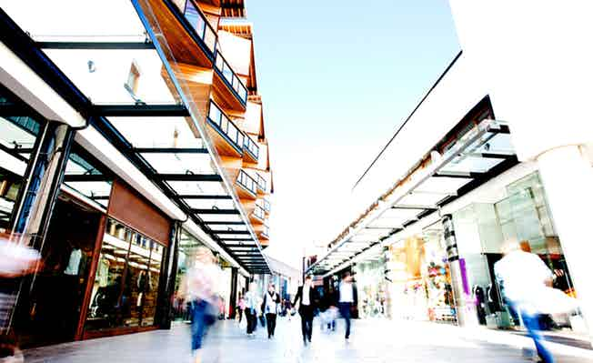 Well-lit UK shopping mall with crowds passing shop