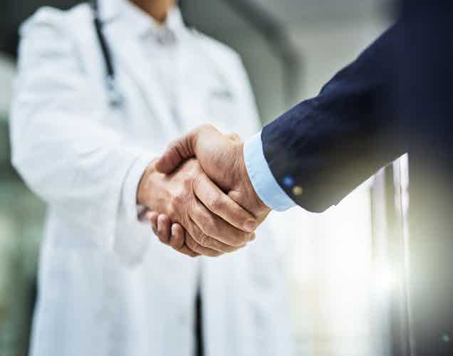 Cropped shot of a doctor shaking hands with a businessman