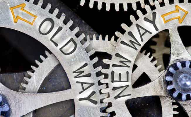 Picture of interlocking cogs with new way and old way stamped on them to illustrate innovation