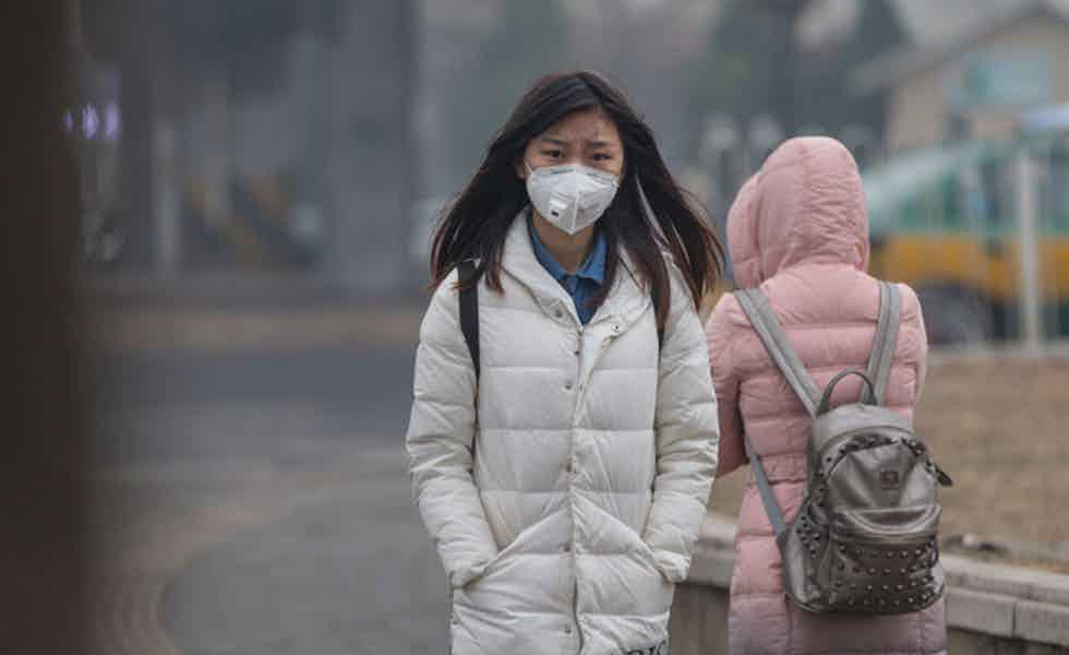 Beijing, China - December 7, 2015: Asian girl protects herself against air pollution by wearing mouth mask with air filter. A incidental people on the background.
