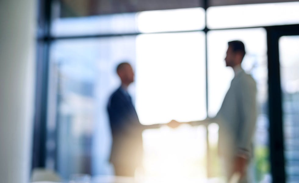 Blurred shot of two businessmen shaking hands in a modern office for feature on international law firms in Ireland