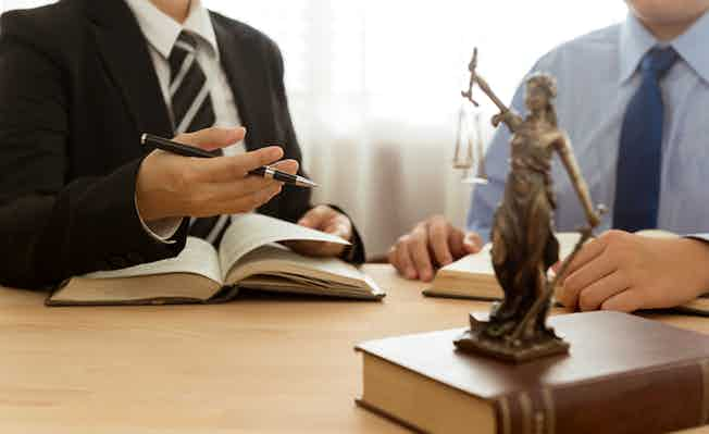 Law, Legal advice, Legislation concept. Lady justice on law book with lawyer and client in law office.