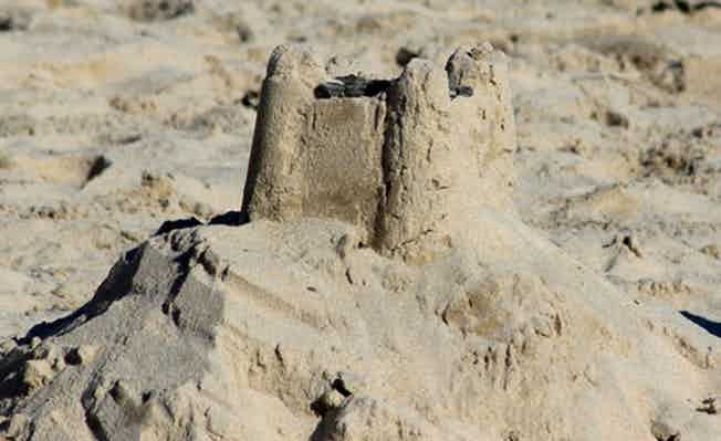Photo showing a mound of sand at the beach, which has a square sandcastle standing at the top and another at the side. The sandcastles have been made with a moulded bucket and spade, which features turrets on the corners.