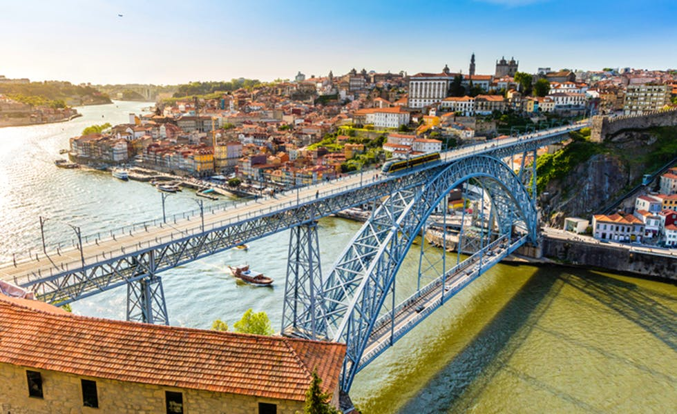 Metro rail seen travelling accross the Dom Luis I bridge that lies over river Douro in Porto city. This is a popular tourist destination and declared a UNESCO world heritage site. The cityscape seen on above and below the bridge.