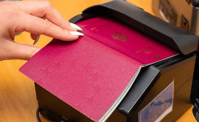 scanning a German biometric passport to register the fact of crossing the state border. Female hand puts a passport to the scanning device. Concept of overseas travel, immigration