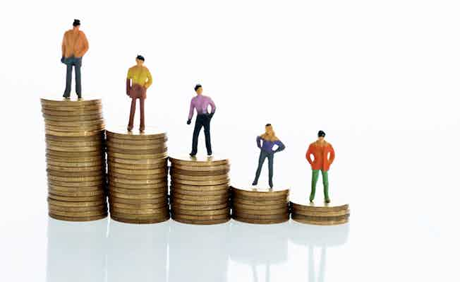 Figurines standing on stack of coins to show salary grades