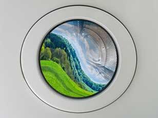 ock photo ID: 1732657280. Concept symbol image greenwashing washing machine with deformed beautiful landscape inside